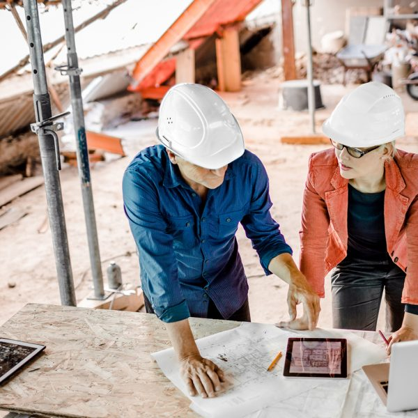 Female architect discussing construction plans with foreman on paper, digital tablet and laptop. Overhead shot.